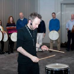 Conor, a professional drummer teaching a rhythm to a group at a Creative Events drum for fun