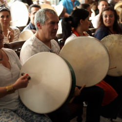 People learning the bodhran at a Creative Events Team Building Event